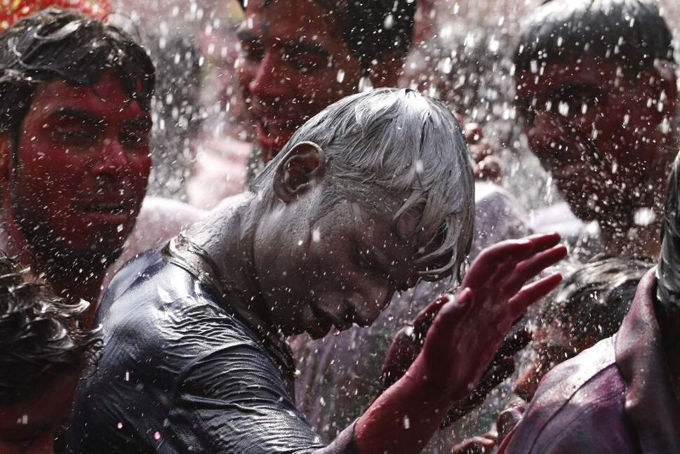 An Indian man, his face smeared with glitter, dances as water is sprayed on him during Holi celebrations in Gauhati, India, Thursday, March 8, 2012. Holi, the Hindu festival of colors, also heralds the coming of spring. (AP Photo/Anupam Nath) (CP)
