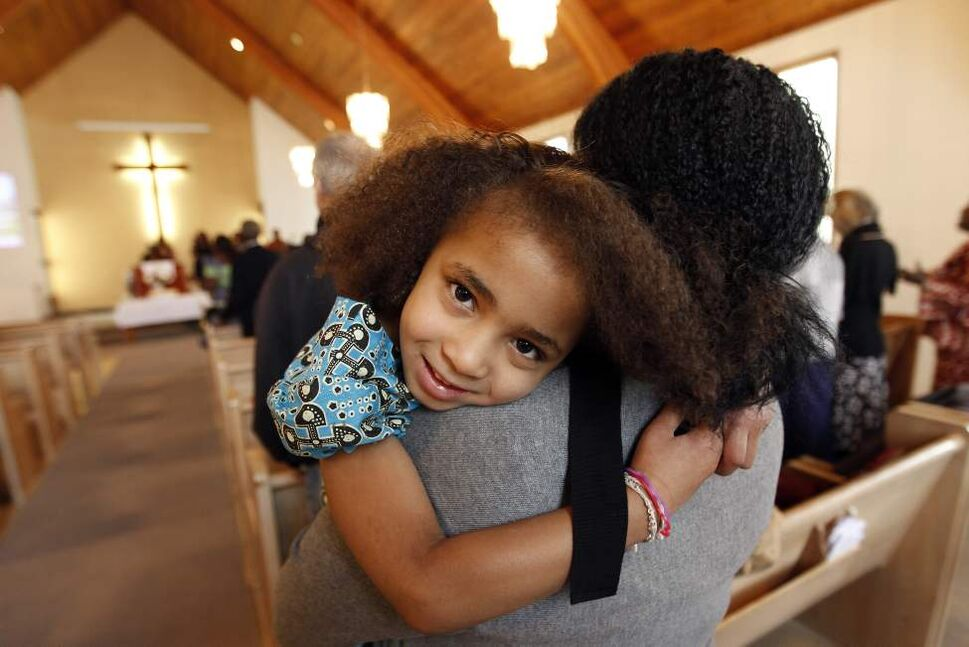 Sabee Larson, 6, sits in the arms of her relative, Maggie Yeboah, during the start of service at Crestview Park Free Methodist Church on Cavalier, January 15, 2012. (TREVOR HAGAN/WINNIPEG FREE PRESS)