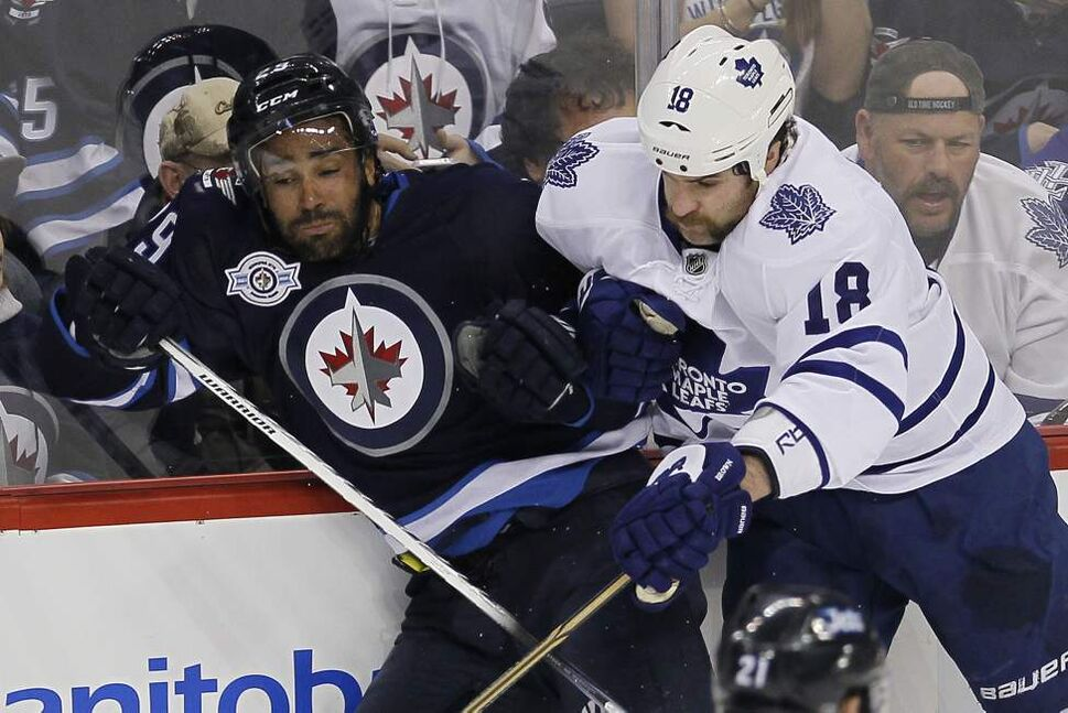 Winnipeg Jets' Johnny Oduya (29) gets hit hard by Toronto Maple Leafs' Mike Brown (18) during first period NHL action in Winnipeg on February 7, 2012. (John Woods / Winnipeg Free Press)