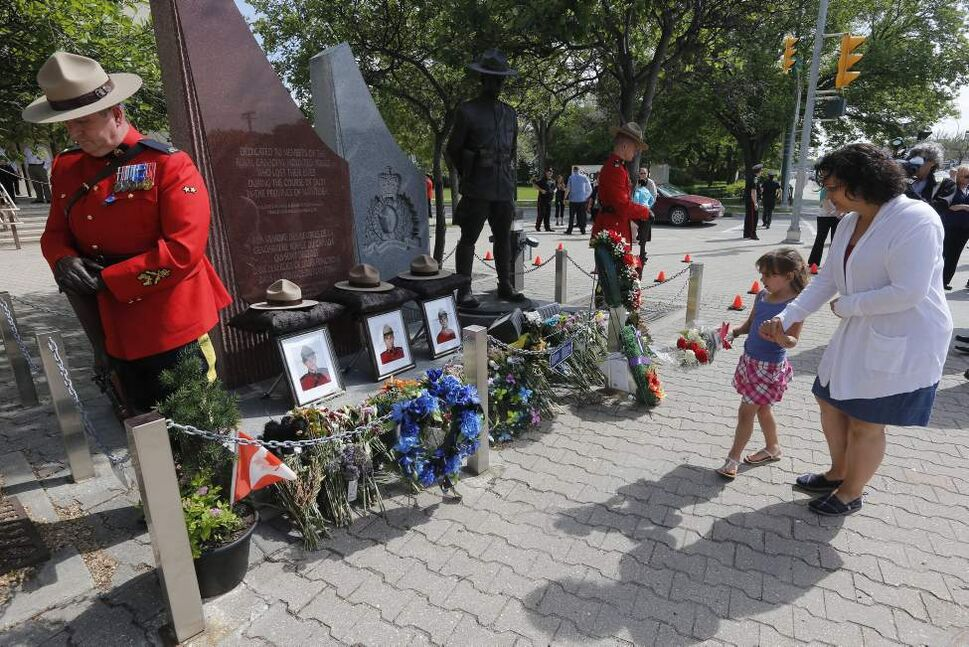 Winnipeg RCMP D Division held their own memorial service for slain members in Moncton NB.  Abigail Bell, 4, with her mother Jacquie Bell, laid a bouquet of flowers at the RCMP memorial for members who lost their lives while on duty . June 10, 2014 (KEN GIGLIOTTI / WINNIPEG FREE PRESS)
