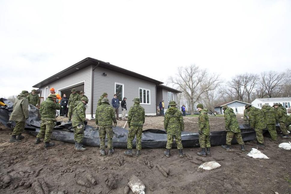 Members of the Canadian Forces surround a home with a water dike close to the Hoop and Holler Bend near Portage La Prairie, Man, Thursday, May 12, 2011.   (THE CANADIAN PRESS/Jonathan Hayward)