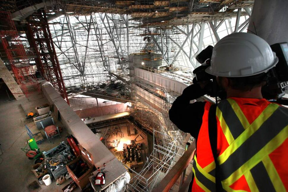 A member of the media takes some shots from one of the viewing areas out into the Cloud - a giant glass structure that surrounds the upper floors of the museum, down into the library sitting area Wednesday morning.  (Ruth Bonneville/Winnipeg Free Press)
