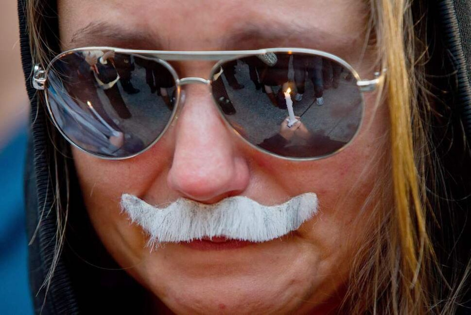 Kathee Reichennek wears a replica of late NDP leader Jack Layton's mustache as a candle is reflected in her glasses during a candlelight vigil for Layton in Vancouver, B.C., on Monday August 22, 2011. Layton passed away early Monday morning in Toronto after a second battle with cancer. THE CANADIAN PRESS/Darryl Dyck