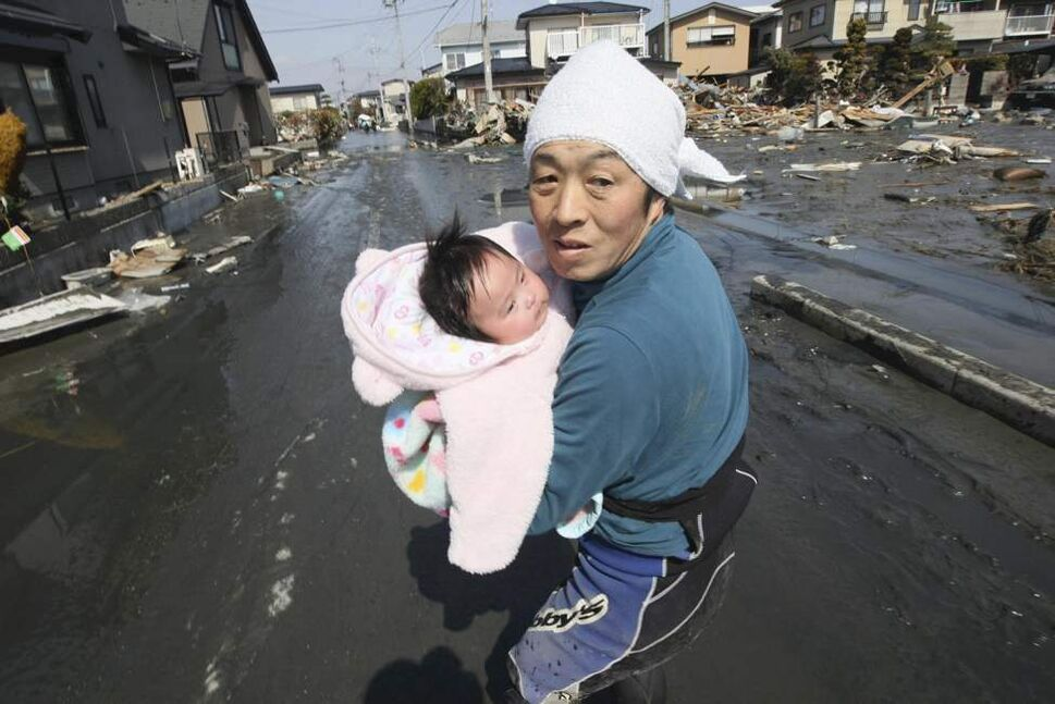 Upon hearing another tsunami warning, a father tries to flee for safety with his just reunited four-month-old baby girl who was spotted by Japan's Self-Defense Force member in the rubble of tsunami-torn Ishinomaki Monday, March 14, 2011, three days after a powerful earthquake-triggered tsunami hit northeast Japan. (AP Photo/The Yomiuri Shimbun, Hiroto Sekiguchi)