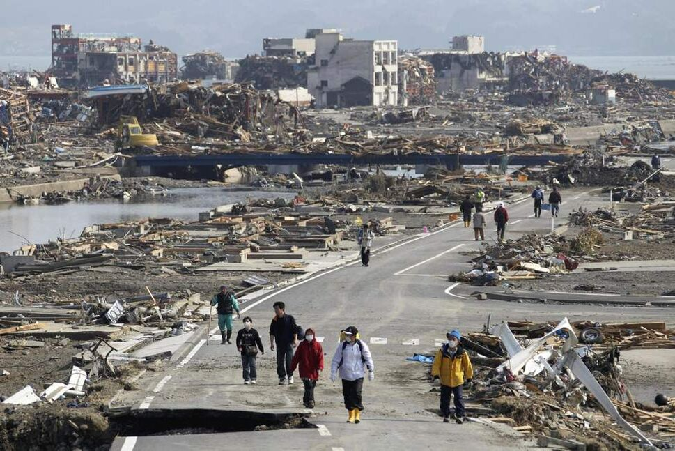 People walk a road between the rubble of destroyed buildings in Minamisanriku town, Miyagi Prefecture, northern Japan, Monday, March 14, 2011, three days after a powerful earthquake-triggered tsunami hit the country's east coast. (AP Photo/The Yomiuri Shimbun, Tsuyoshi Matsumoto)