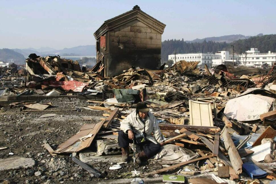 A tsunami survivor sits down in the rubble in Yamadamachi in Iwate Prefecture Monday, March 14, 2011, three days after a powerful earthquake-triggered tsunami hit the country's east coast. (AP Photo/The Yomiuri Shimbun, Takashi Ozaki)