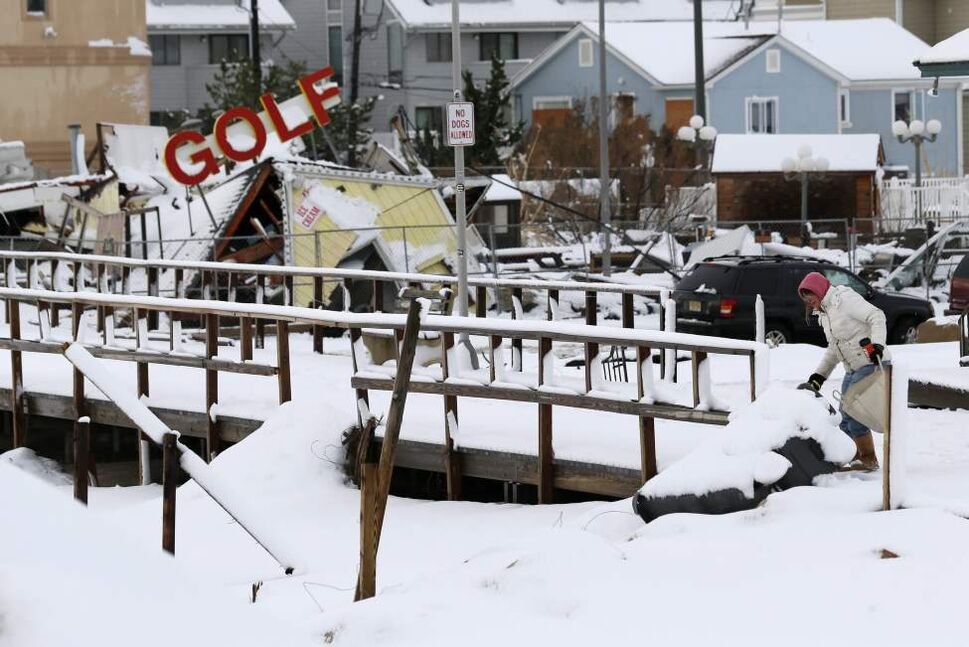 A woman tosses trash into a trash can as debris from a miniature golf course lay cover in snow behind her at Jenkinson's Boardwalk, Thursday, Nov. 8, 2012, in Point Pleasant, N.J. The Nor'easter appeared to have done little new damage to the already badly scarred Jersey Shore. (AP Photo/Julio Cortez)