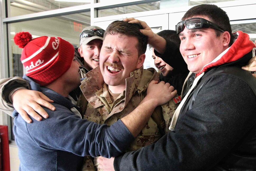 Master Bombardier Nathan Cousineau (centre) of the 116 Independent Field Battery out of Kenora is greeted by friends Shaun Magill (left) and Kevin Weirsema after arriving in Winnipeg at 17 Wing from Afghanistan on Monday. (Mike Deal / Winnipeg Free Press)