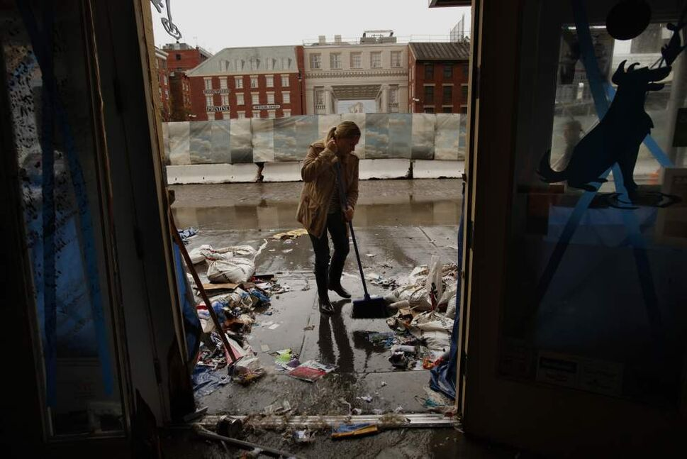 "Amanda Zink starts to clean up the store she owns called ""The Salty Paw,"" which was completely flooded on the waterfront of lower Manhattan, Tuesday, October 30, 2012. The tape on the windows was no match for the strength of the storm. Hurricane Sandy caused major damage to New York City and surrounding areas.  (Carolyn Cole/Los Angeles Times/MCT)"