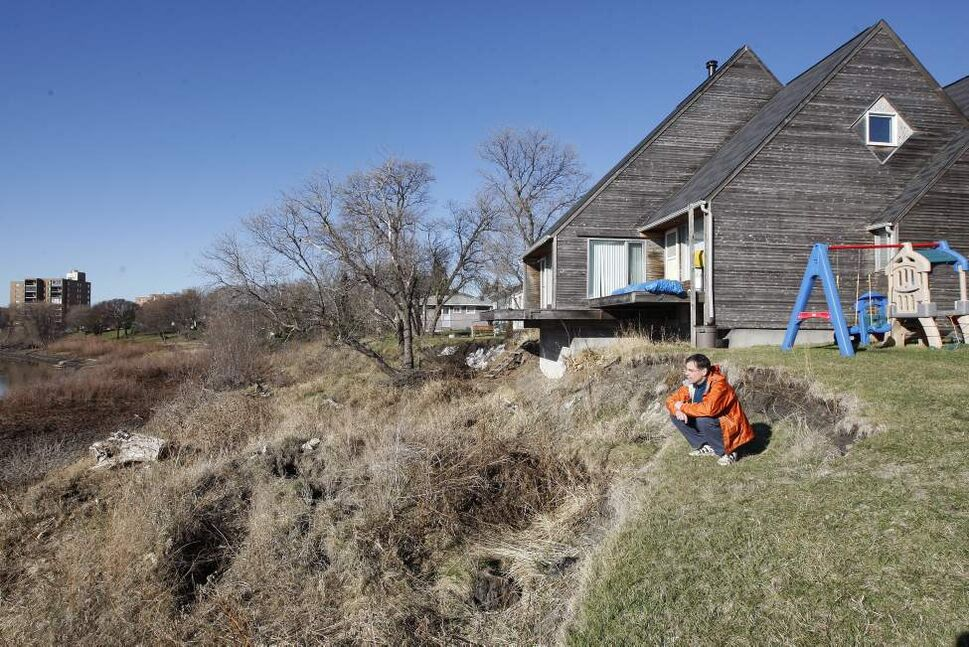 Riviera Crescent  resident Wolfgang Jansen kneels on the river bank slowly creeping in on his home. Jansen is battling with the city over the erosion issue and what he says is their lack of action to repair it. (KEN GIGLIOTTI  / WINNIPEG FREE PRESS)