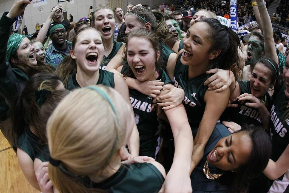 Members of the Vincent Massey Trojans celebrate a win over the the Sisler Spartans in the MHSAA AAAA girls' provincial basketball championships at the University of Manitoba. March 24, 2014    (John Woods/Winnipeg Free Press)