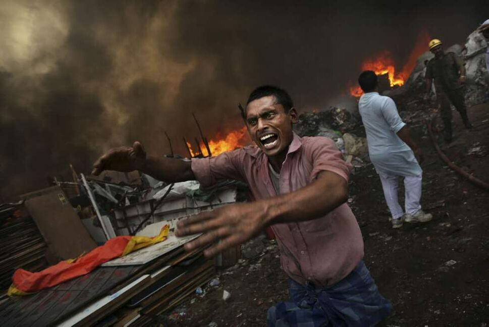 An Indian shouts for water as a shanty town is engulfed in flames in New Delhi, India. A fire swept through a slum, destroying hundreds of shanties where residents had collected scrap plastic and rubber for resale. No one was reported injured or killed, fire department chief A.K. Sharma said. (AP Photo/Kevin Frayer)