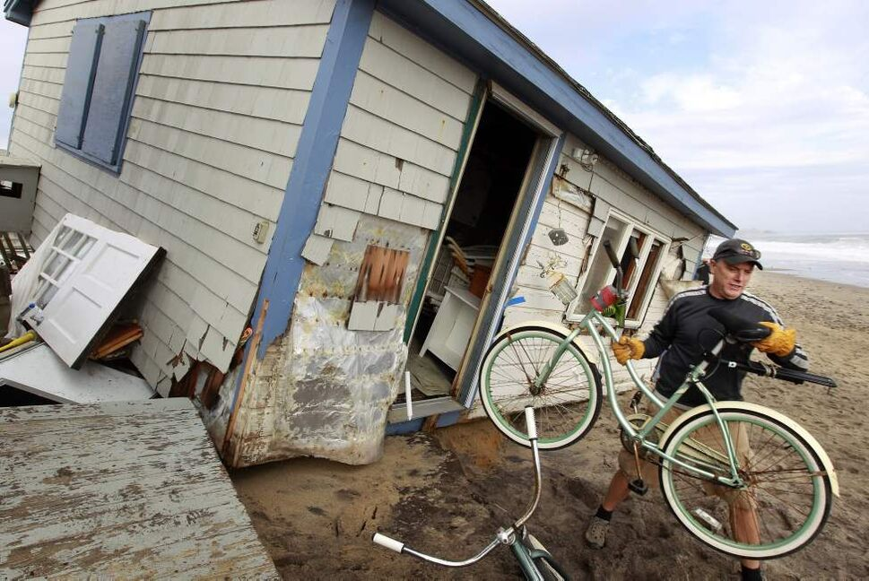Pete Duhamel, of South Kingstown, R.I. removes a bicycle from a cottage while helping a friend salvage belongings from the structure destroyed by Superstorm Sandy, on Roy Carpenter's Beach, in the village of Matunuck, in South Kingstown, Tuesday, Oct. 30, 2012. Sandy, the storm that made landfall Monday, caused multiple fatalities, halted mass transit and cut power to more than 6 million homes and businesses. (AP Photo/Steven Senne)