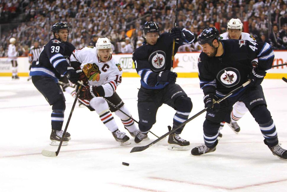 Zach Bogosian (second from right) tries to get the puck out of the Jets zone during the first period as (from left) Toby Enstrom, Jonathan Toews, James Wright and Marion Hossa scramble for the puck.
