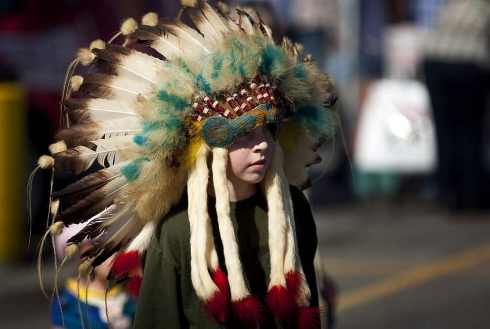 A young boy wears an Indian headdress during a Calgary Stampede breakfast in Calgary. This is the 100th anniversary of the Stampede which runs for 10 days featuring rodeo action, chuckwagon races, a midway, agricultural exhibits and live stock competitions. (The Canadian Press / Jeff McIntosh)