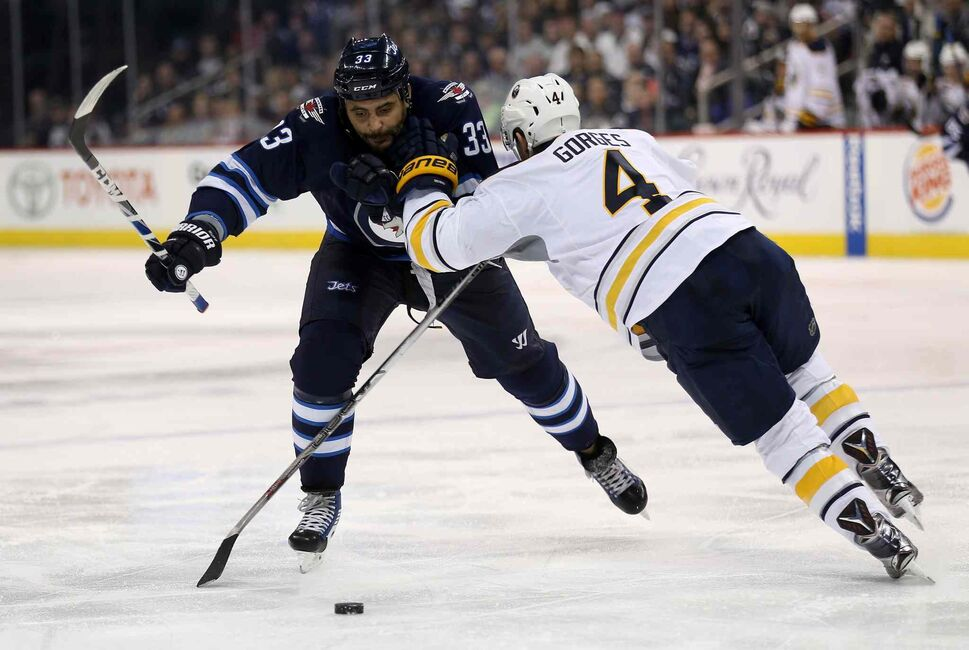 Winnipeg Jets' Dustin Byfuglien (33) carries the puck past Buffalo Sabres' Josh Gorges (4) during the second period. (Trevor Hagan / The Canadian Press)