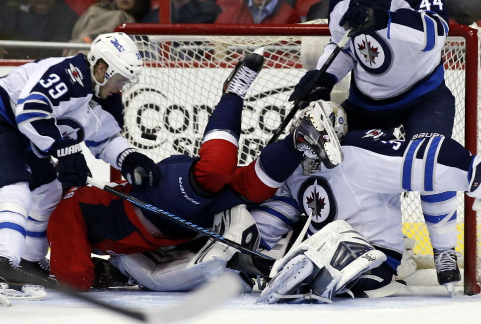 Washington Capitals' centre Nicklas Backstrom falls in front of Winnipeg Jets' goalie Ondrej Pavelec (31) as the puck, shot by right wing, Alex Ovechkin goes into the net, with defenceman Tobias Enstrom (39) at left during the third period of Thursday's game in Washington. The Capitals won 4-2.  (Alex Brandon / The Associated Press)