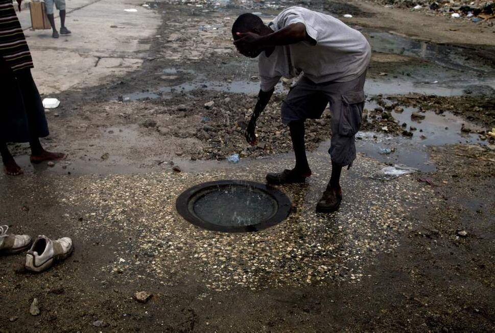 A man wipes his face in a sewer system In Port-au-Prince, Haiti, Monday, Aug. 23, 2010. (Ramon Espinosa / The Associated Press)