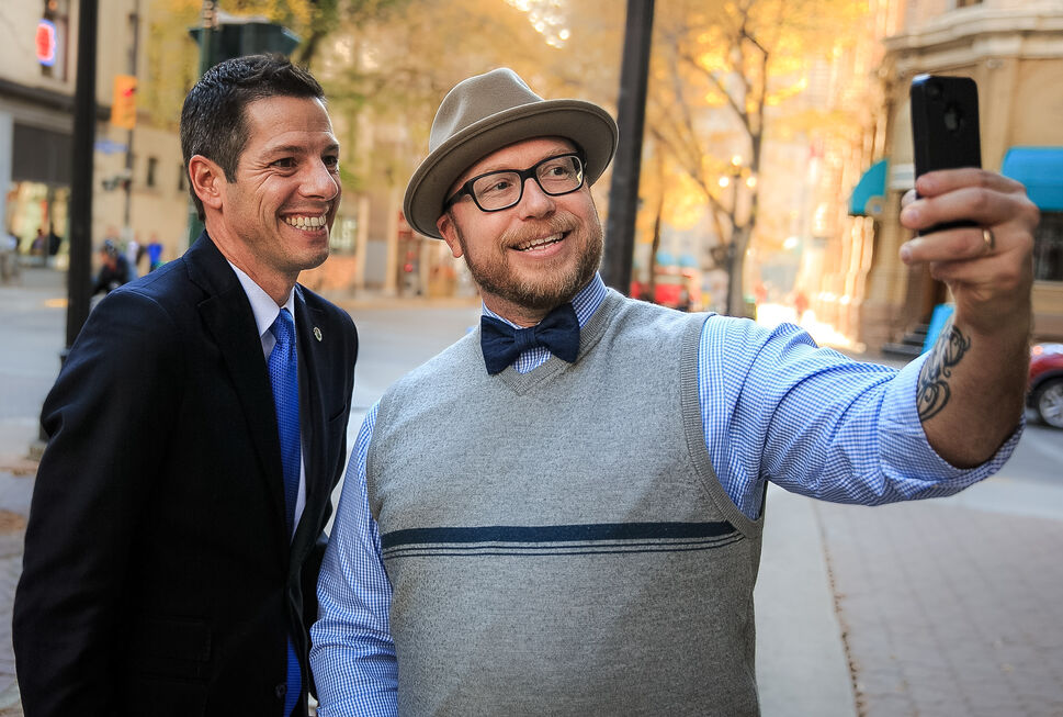 Luke Nolan snaps a selfie with mayor-elect Brian Bowman the morning after his election win. In a short walk in the Exchange District a dozen people stopped to congratulate Bowman the day after the October election.  (Melissa Tait / Winnipeg Free Press) (Melissa Tait / Winnipeg Free Press)