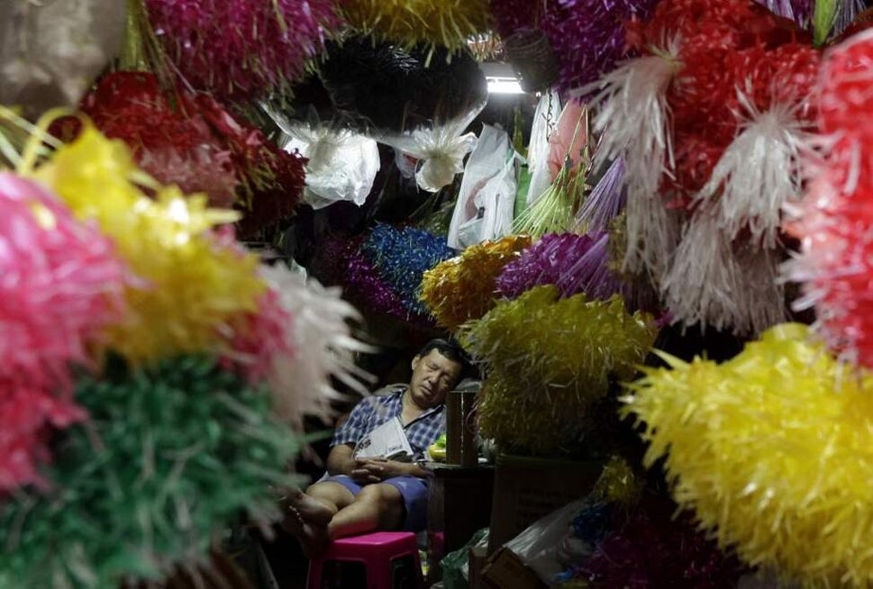 A vendor takes a nap at a flower shop in Bangkok, Thailand. (AP Photo/Xinyan Yu)