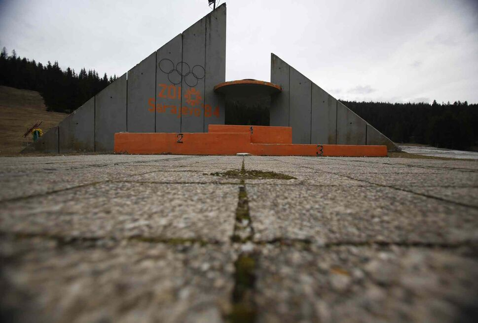 "A concrete podium for winners with the text ""Winter Olympic Games 1984"" stands abandoned near jumping hills at Mt. Igman near the Bosnian capital of Sarajevo.  (Amel Emric / The Associated Press)"