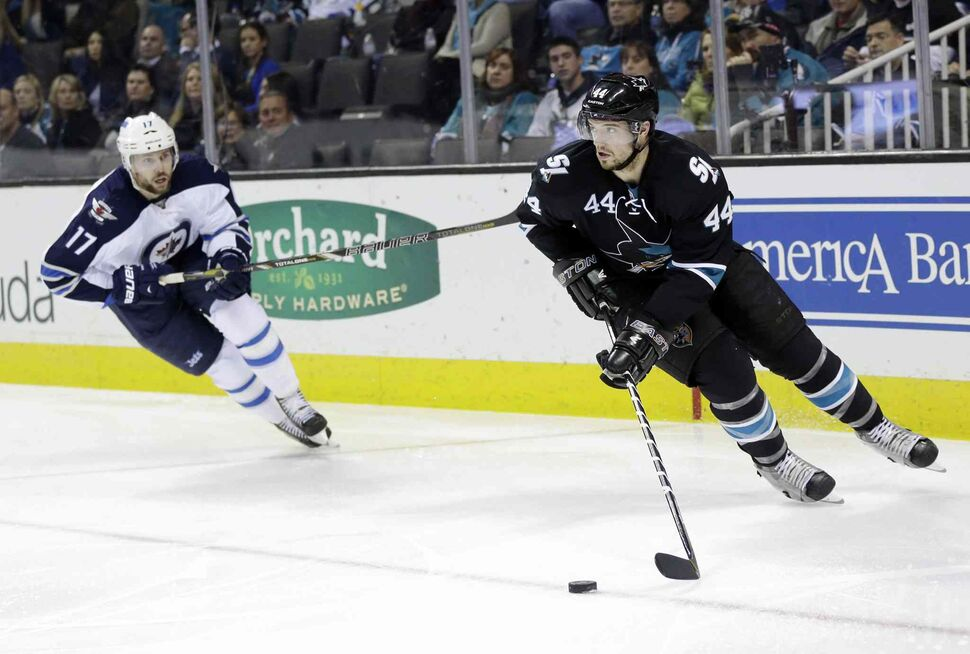 San Jose Sharks' Marc-Edouard Vlasic (44) is chased by Winnipeg Jets' James Wright (17) during the second period Thursday's game. The Sharks won 1-0. (Marcio Jose Sanchez / The Associated Press)