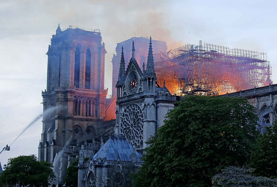 A firefighter tackles the blaze as flames and smoke rise from Notre Dame cathedral as it burns. (Michel Euler / The Associated Press)