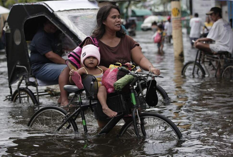 A Filipino girl rides a bicycle along a flooded street at Valenzuela city, north of Manila, Philippines on Tuesday July 31, 2012. Typhoon Saola dumped torrents of rain as it swept past the Philippines, killing at least seven people and displacing more than 20,000 others by Tuesday.  AP Photo / Aaron Favila