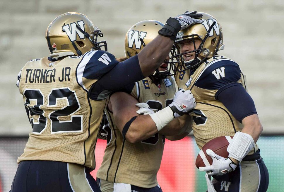 Winnipeg Blue Bombers' Robert Marve, right celebrates a touchdown with teammates Bryant Turner Jr., and Michel-Pierre Pontbriand as the Bombers face the Montreal Alouettes during the first quarter of Friday's game. (Paul Chiasson / The Canadian Press)