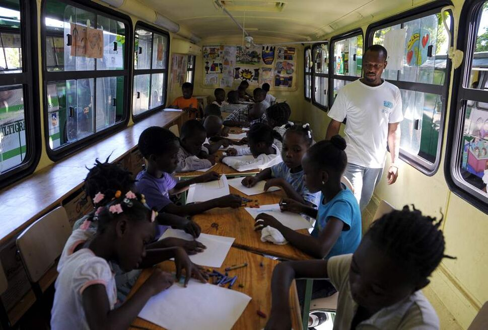 Art teacher Joel Saint Juste oversees his students drawing pictures at the Plas Timoun school for traumatized victims of the earthquake. Buses from the Dominican Republic have been transformed into classrooms.  (Ricky Carioti / Washington Post)