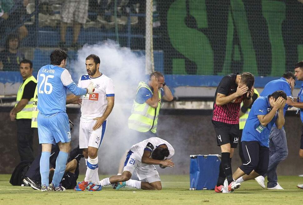 In this Sunday, Oct. 21, 2102, a powerful firecracker exploded near players and trainers of Anorthosis Famagusta which was thrown from Omonias fans during a soccer match between Anorthosis Famagusta and Omonia Nicosia at Antonis Papadopoulos stadium in Larnaca, Cyprus. Trainers were tending to Colombian forward Ricardo Laborde on Sunday. Video footage shows the trainers and Laborde writhing on the ground after the firecracker exploded inches from their faces. (AP Photo/Sakis Savides)