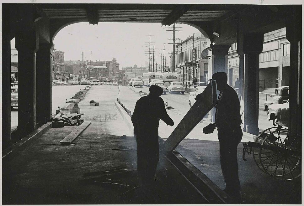 WINNIPEG FREE PRESS FILES Pillars of the north Main Street subway, under the C.P.R. tracks, form a frame for two workers as they put the finishing touches on a section of a paving job expected to greatly ease a traffic bottleneck in October 1955. The pavement, which replaced the streetcar tracks, provided two additional lanes for automobiles.