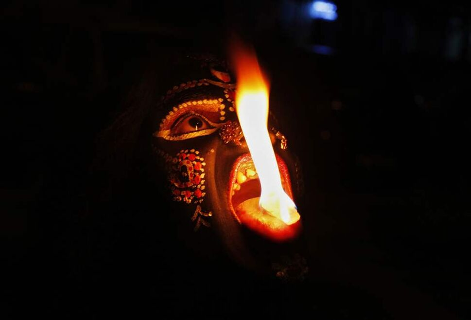 In this, Sunday, Oct. 21, 2012 photo, an Indian performer disguised as Hindu Goddess Kali performs with fire during Navratri festival in Allahabad, India. Navratri or the festival of nine nights is an annual Hindu festival of worship and dance. (AP Photo/Rajesh Kumar Singh)