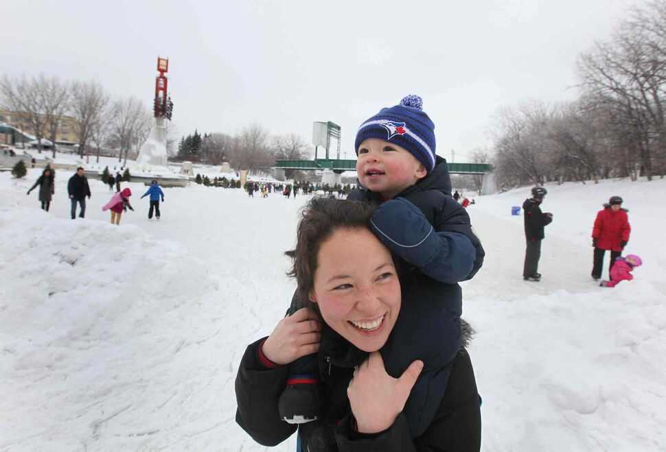 Fourteen-month-old Owen Wilkinson watches a train go over the train bridge while his mother carries him on the new Red River Mutual Trail Saturday afternoon.   (Ruth Bonneville / Winnipeg Free Press)