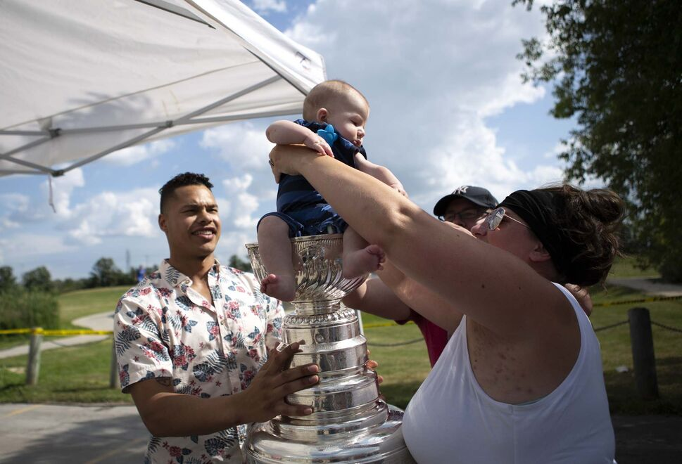Five-month-old Zane Spittal is lifted into the Stanley Cup by him mother Kara for a photo with Washington Capitals defenceman Madison Bowey after waiting two hours to see him during his home town tour with the cup. (ANDREW RYAN / WINNIPEG FREE PRESS</p>)