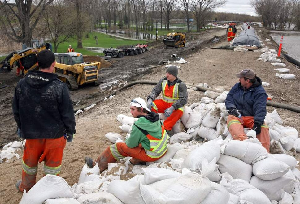 Brandon Sun Civic employees wait to deliver sandbags on a dike set up on John Avenue, Thursday afternoon. May 12, 2011(Colin Corneau/Brandon Sun)