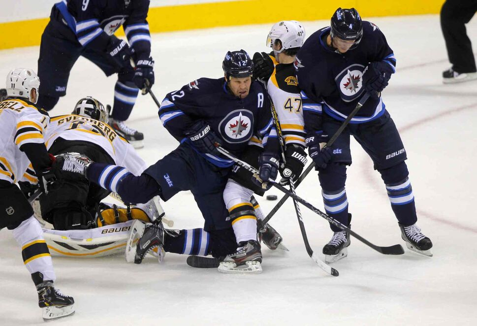 Olli Jokinen (centre) and Paul Postma (right) squeeze Torey Krug off the puck. (BORIS MINKEVICH / WINNIPEG FREE PRESS)