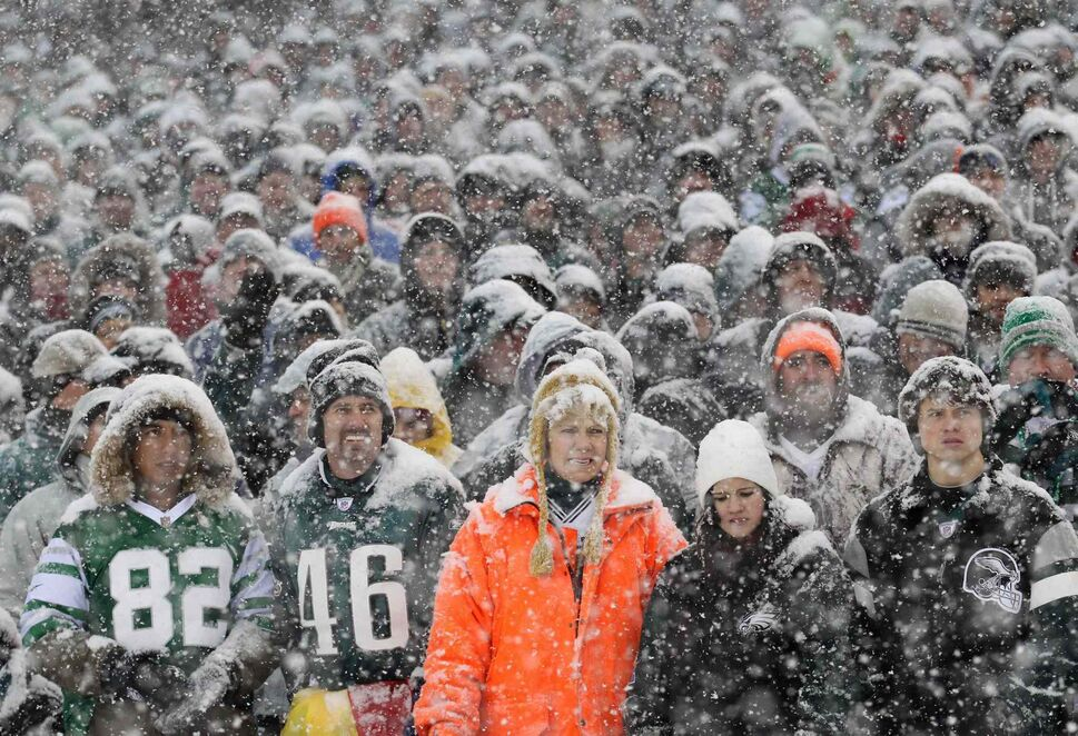 Fans watch the Philadelphia Eagles play the Detroit Lions as snow falls during the first quarter of Sunday's NFL football game in Philadelphia. (Yong Kim / The Associated Press)