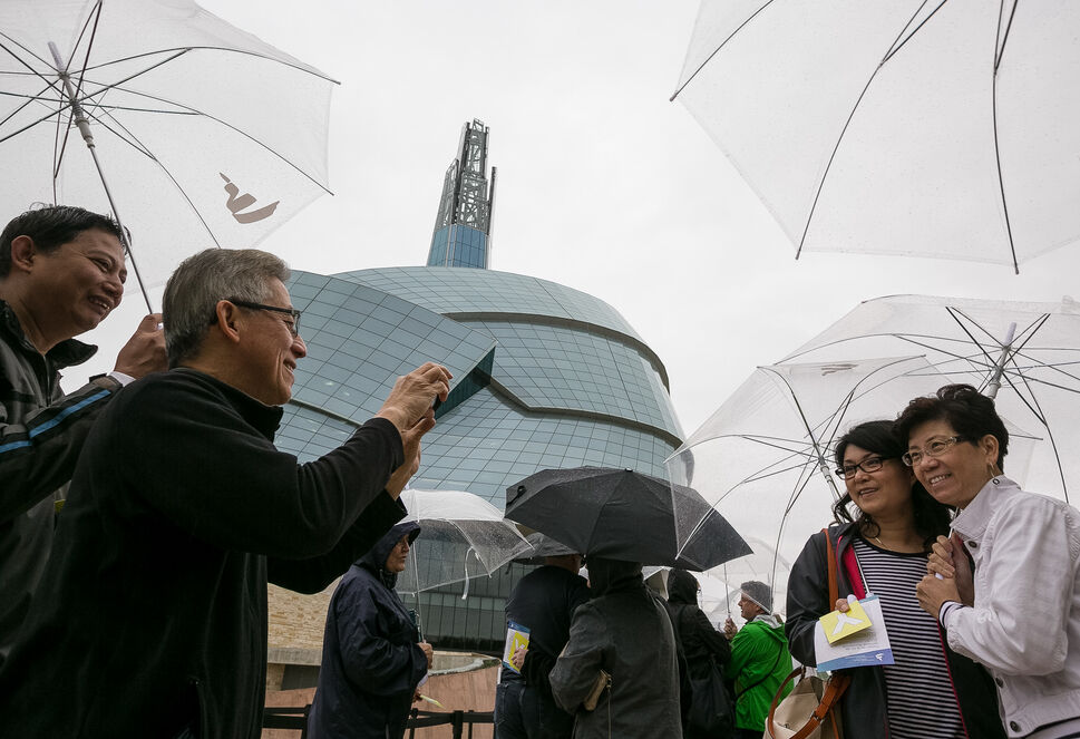 Frank Yong snaps a photo of his wife Teresa and her friend Jenny Lee, all from B.C., while they wait in the light rain for their preview tour at the Canadian Museum for Human Rights. The rain kept away some of the people with reserved tickets, allowing walk-ups to gain access to the guided tour of four of 11 galleries.  Saturday, September 20, 2014  (Melissa Tait / Winnipeg Free Press)