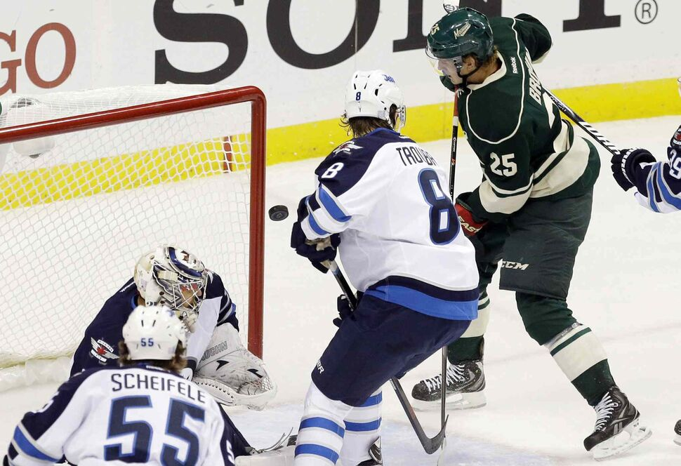 The puck glances off the glove of Minnesota Wild's Jonas Brodin (25) as he scores against Winnipeg Jets goalie Ondrej Pavelec in the first period. The goal was reviewed, and it was determined to count as a good goal. (Jim Mone / The Associated Press)