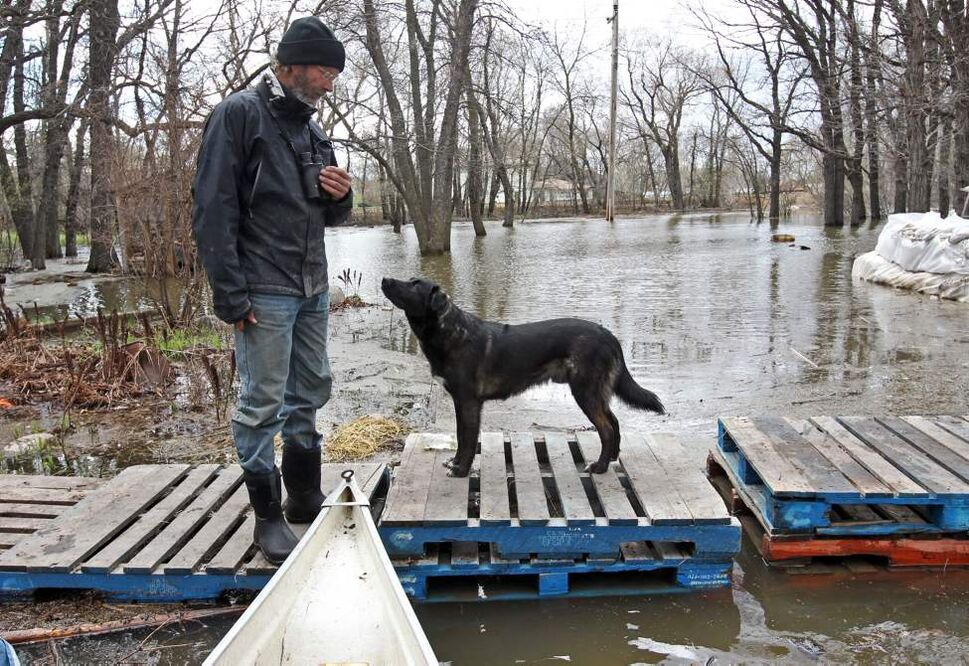 Dave Barnes, with his dog Jack, looks over the expanse of flood water covering his east-end property, Wednesday afternoon. Friends and volunteers helped Barnes surround his home with sandbags and protect it from the surging Assiniboine River. May 11, 2011 (Colin Corneau/Brandon Sun)
