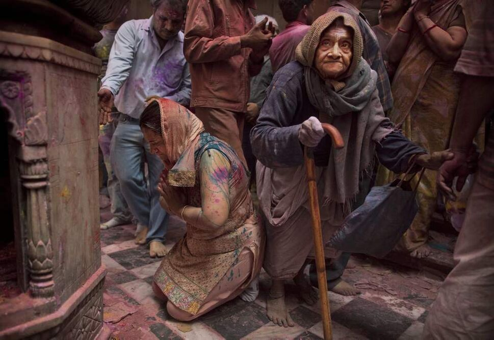 "An elderly Hindu devotee walks past a woman praying as they gather to mark ""Holi,"" the festival of color, at the Banke Bihari temple in Vrindavan, about 140 kilometers (87 miles) from New Delhi, India, Thursday, March 8, 2012. Vrindavan is a famous place for Holi celebrations, where according to legend, the Hindu god Krishna played Holi with his consort Radha. (AP Photo/Kevin Frayer) (CP)"