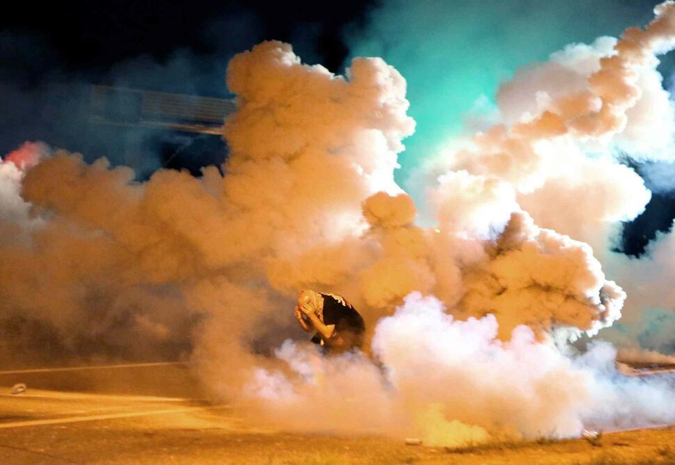 A protester takes shelter from the tear gas exploding around him Wednesday. (David Carson/ Tribune Media)