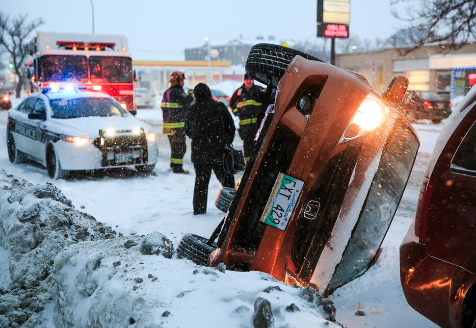No one was injured in a car rollover on Henderson Highway near Greene Avenue. The vehicle collided with the snowbank and rolled, landing to rest barely a half-metre behind Thomas Oliveira's parked van. Oliveira, who lives nearby, didn't hear the collision, but saw out his window a driver being helped out of the passenger window by a group of passersby.   (Melissa Tait / Winnipeg Free Press)