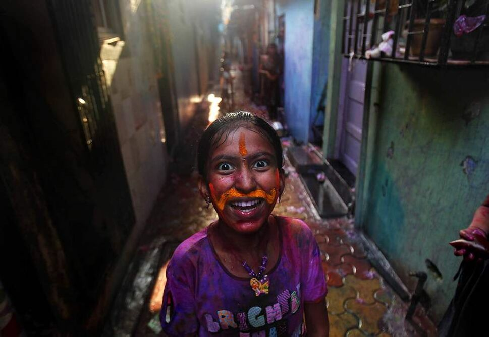 An Indian girl, her face smeared with colored powder, reacts to the camera during Holi celebrations in Mumbai, India, Thursday, March 8, 2012. Holi, the Hindu festival of colors, also heralds the coming of spring. (AP Photo/Rafiq Maqbool) (CP)