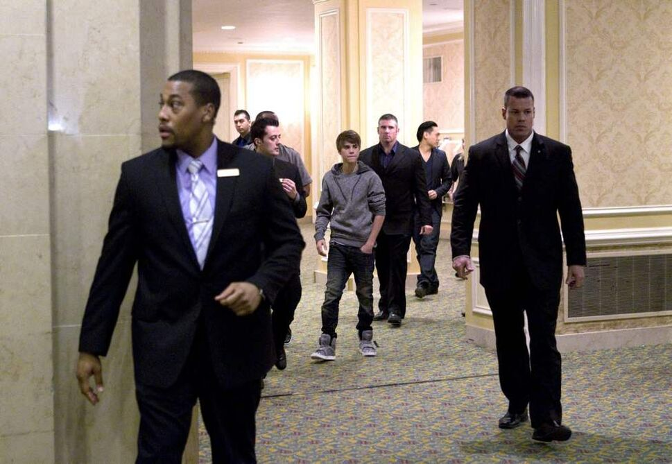 Pop star Justin Bieber (centre) is surrounded by security guards as he leaves a press conference to promote his new film 'Never Say Never' in Toronto on Tuesday, February 1, 2011.THE CANADIAN PRESS/Chris Young