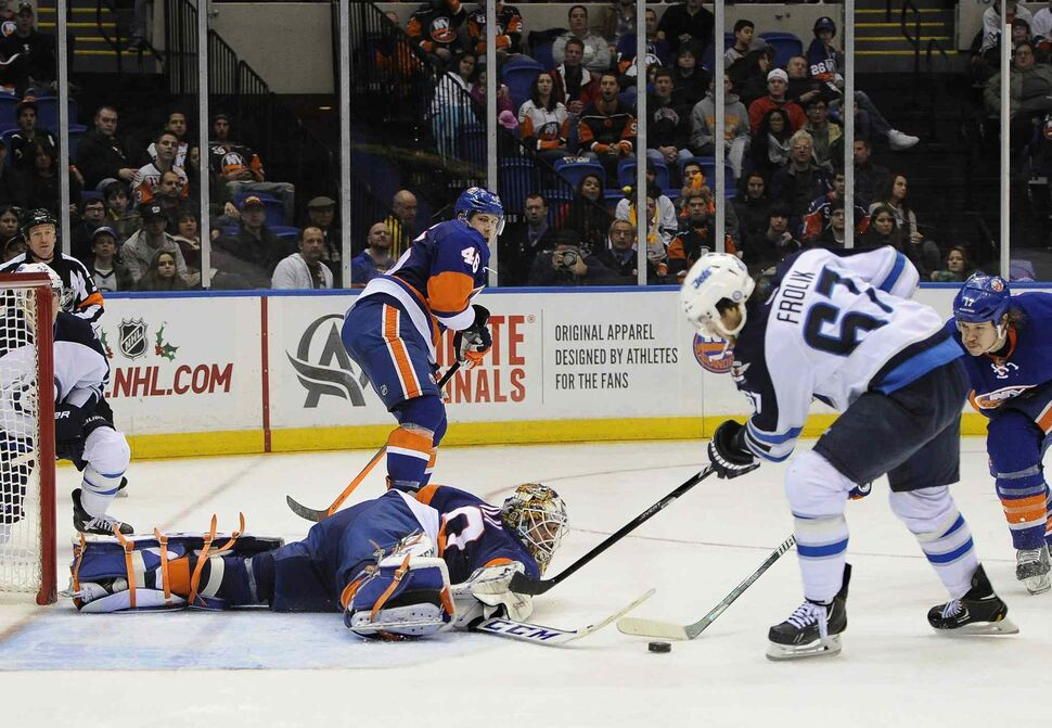 New York Islanders goalie Kevin Poulin (bottom) dives to block a shot on goal by Winnipeg Jets' Michael Frolik (67) as Matt Martin (right) defends from behind in the third period. (Kathy Kmonicek / The Associated Press)