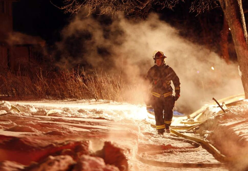 Winnipeg fire fighter walks through exhaust fog created by a pumper truck suppling water to a Horton Ave. house fire. January 21, 2014  (KEN GIGLIOTTI / WINNIPEG FREE PRESS)
