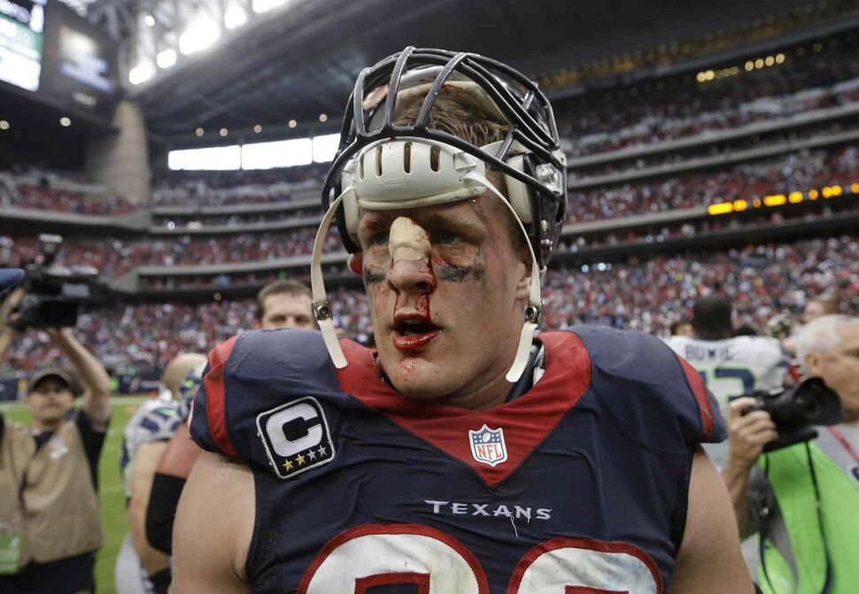 A bloodied but unbowed Houston Texans J.J. Watt walks off the field after the team's 23-20 overtime loss to the Seattle Seahawks in Houston on Sunday. (CP)