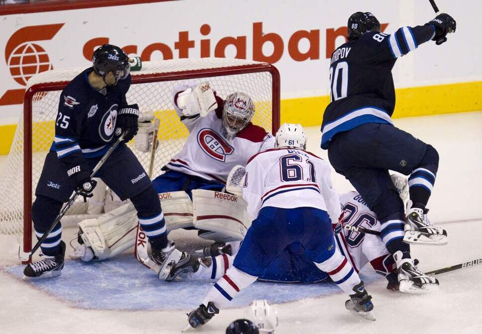 Winnipeg Jets' Nik Antropov scores a goal past Montreal Canadiens goalie Carey Price and Canadiens defenceman Raphael Diaz during the third period. (Jonathan Hayward / The Canadian Press)
